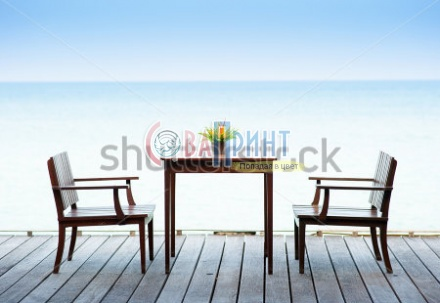 stock-photo-terrace-sea-view-with-outdoor-wood-chairs-and-table-168323384