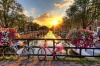 stock-photo-beautiful-sunrise-over-amsterdam-the-netherlands-with-flowers-and-bicycles-on-the-bridge-in-spr
