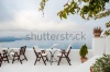 stock-photo-cafe-on-the-terrace-with-a-beautiful-sea-view-foggy-morning-white-architecture-on-santorini-227087314